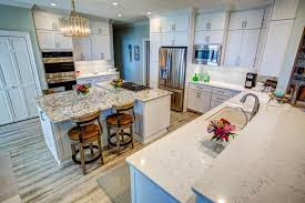 white shaker cabinets with quartz countertops. sleek modern kitchen with stacked shaker cabinets, quartz countertops and glass subway tile backsplash white cabinets