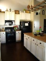 Black Appliances With White Cabinets In The Kitchen