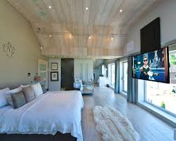 bedroom with tv. Example Of A Large Trendy Master Light Wood Floor Bedroom Design In London With Beige Walls Tv R