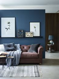 chic seating area with a brown sofa and a navy accent wall and textiles  Blue  Living ...