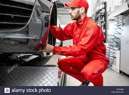 Red Checking Auto Mechanic In Red Uniform Servicing Sports Car Checking