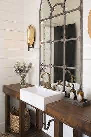 rustic industrial bathroom with a drak stained reclaimed wood vanity and a  shelf for storage