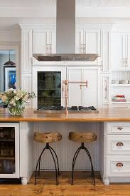 stunning kitchen features white raised panel cabinets adorned with copper hardware framing a glass door refrigerator