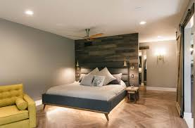 funky contemporary master suite bedroom with barn board wall lighted platform bed and herringbone wood