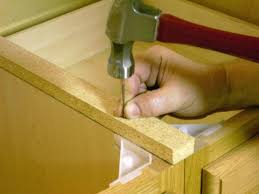 photo showing build up stick being nailed to cabinet