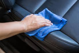 hand with microfiber cloth cleaning interior modern car