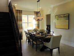 exclusive black marble dining table with beautiful two hanging glamorous home room chandeliers over long wooden