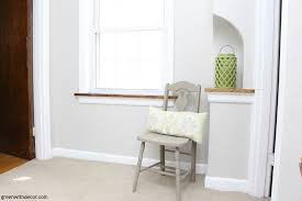 a neutral hallway with agreeable gray walls a big window with a wood window sill