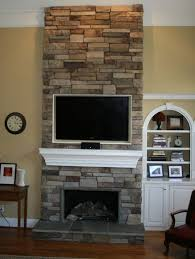 impressive stone fireplace with wide tv above combined white wood mantle for classic living room design awesome stone fireplace ideas stone fireplace