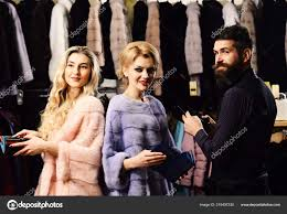 women in violet and pink fur coats with male assistant girls wear mink fur coats near macho las ping concept friends ping in luxury fur