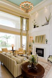 Bright yellow and white color scheme of this living room helps natural  light illuminate the large