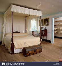 Antique four-poster bed with cream drapes and linen in country Stock ...