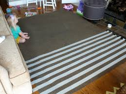 now for the fun part bring on the spray paint i laid the rug out on my roof using drop cloths around the edges i started with the neon pink paint on