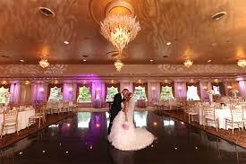 couple kissing underneath il tulipano s tulip chandeliers in grand ballroom