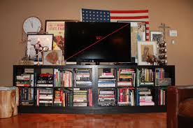 black Ikea Expedit Bookcase filled with book plus tv above ideas with  american flag and tan