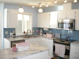 favored white kitchen cabinet system added small kitchen island with white marble top also glass blue subway tile backsplash in white and blue kitchen