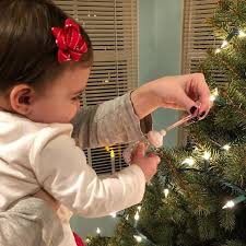hanging up her first ornament hallmark babysfirst santababy tistheseason tree marrujo tree