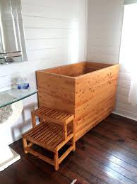 fashionable outdoor soaking tub bathroom with natural wood deep soaking bathtub near small bench seat small fashionable outdoor soaking tub