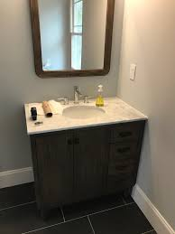 i ultimately installed the vanity flush with the wall and botched the baseboard behind the vanity i ripped down some baseboard mostly to prevent crud from
