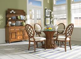 dining room curving brown wooden base with round glass table combined with brown wooden chairs