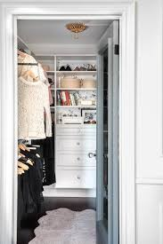 white walk in closet with gold flush mount