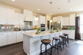 pendant progress lighting for elegant kitchen design with white kitchen cabinetosaic tile backsplash plus super white granite countertop and