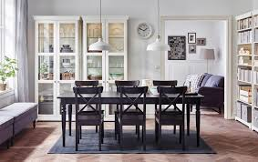 a large dining room with a black extendable dining table with chairs and gldoor cabinets in
