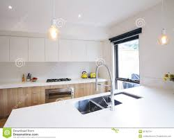 Modern Kitchen With Pendant Lighting And Sunken Sink Stock Photo - Modern kitchen pendant lights