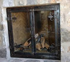 mountain rustic fireplace doors with large hand forged hinge accents and bronze patina finish