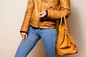 a woman wearing jeans carrying a leather purse