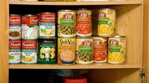 wooden kitchen cupboard with shelves full of canned soup and vegetables