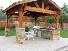 shiny black marble countertops wall mounted tv covered outdoor kitchen design ideas stainless steel pyramid range