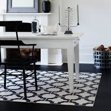 dining room with black and white rug effect flooring with white dining table black