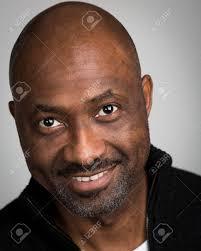 Portrait Dun Homme Noir Rasé Chauve Avec Une Moustache Porter Un Cardigan Noir Isolé Sur Un Fond Gris