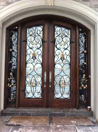 high double brown wooden doors with glass on the middle plus curving black steel and golden