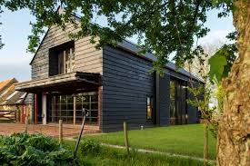 ... folds upwards to create a canopy for the large brick terrace just  outside the living room and large shutters designed to suggest barn doors  slide back ...