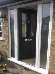 black posite entry door with white frame and double windows