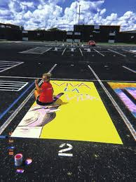 key club president amber seeley a senior paints her parking spot in the student
