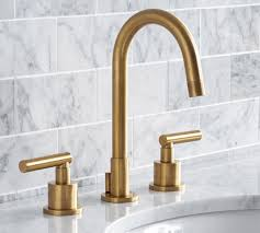 brushed brass faucet in a marble bathroom