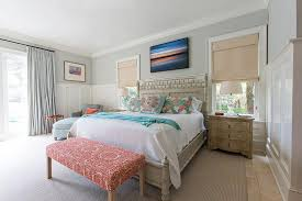 gray bamboo bed with aqua and red pillows