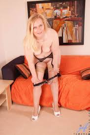 Mature blonde in sheer nylons and black garter belt masturbates.