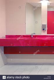 large public bathroom. public toilet interior with red sink and large mirrors bathroom