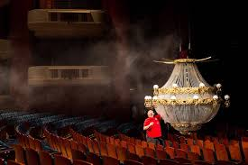 a crew member works on a pivotal phantom of the opera prop the