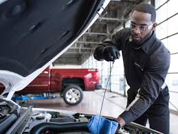 buick chevrolet and gmc service center for bloomington and bedford service technician checking vehicle oil