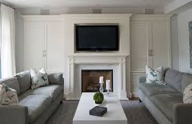 beautiful living room with creamy white built in cabinets on either side of the traditional marble fireplace