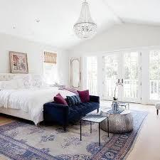 white glass beaded chandelier over blue velvet tufted sofa at foot of bed
