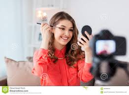 makeup and people concept happy smiling woman or beauty ger with eye shadow brush mirror and camera recording makeup tutorial video at home