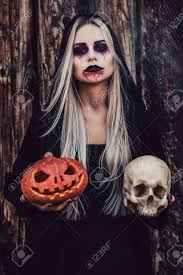 portrait of black witch with scary makeup in black mantle on wooden background