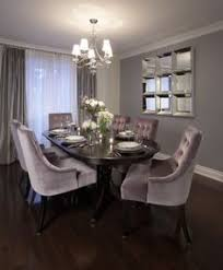 dining room with wall mirror chandelier dark wood table and purple tufted dining chairs