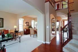 Open Floor Plan Living Room Furniture Arrangement Brown Wooden Floor Under Large White Rug Connected By Beige Wall